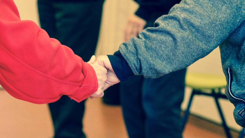 Personnes âgées en maison de retraite qui se tiennent par la main.