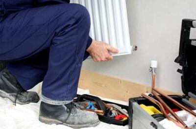 Artisan chauffagiste en train de faire des réparations dans une maison.