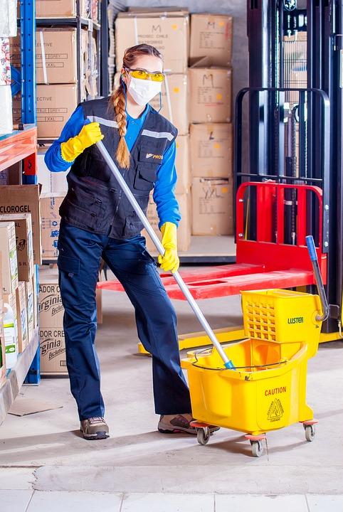C'est une employée de ménage qui nettoie avec un seau et une serpillière.